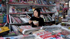 Kiinalainen sanomalehdenmyyjä kioskissaan
