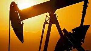 Pumppaava öljykaivos kuvattuna vastavaloon aamunkoitossa. Kullankeltainen aurinko nousee, öljykaivostorni siluetissa.