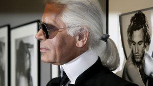 Karl Lagerfeld poseraa mustissa aurinkolaseissaan oman valokuvanäyttelynsä töitä vasten.
