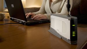 Nainen käyttää tietokonetta, jonka vieressä langattoman 450-laajakaistaverkon modeemi.