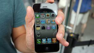 Mies pitelee iPhone 4 -puhelinta