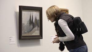 Nainen tarkastelee taulua museossa.