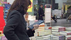 Nainen lukee kirjan takakantta kirjakaupassa