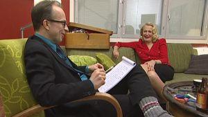 Simo Frangen Miitta Sorvalin esittämän sosiaalipsykologin Miitta-tädin vieraana. Istuvat sohvalla.