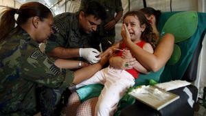 Brasilian ilmavoimien henkilökunta antaa nesteytystä pikkulapselle Rio de Janeirossa Brasiliassa huhtikuussa 2008.