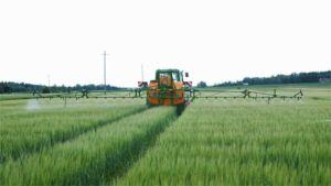 Traktori ruiskuttaa torjunta-ainetta pellolle.