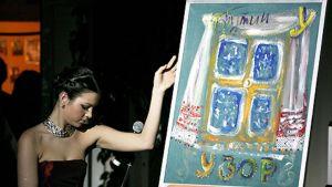 Nainen esittelee Vladimir Putinin maalaamaa teosta, joka myytiin 17. tammikuuta 850 000 eurolla.