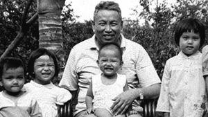 Mustavalkoinen kuva, jossa Pol Pot ja nejä lastenlasta katsoo kameraan silmiään siristellen.
