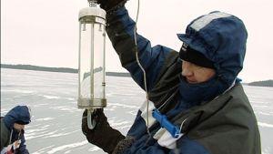 Tutkija nostaa vesinäytesäiliötä