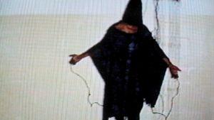 Irakilaisen vangin pää on peitetty hupulla ja käsiin on kytketty sähköjohdot
