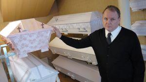 Yrittäjä Markku Lindholm esittelee hautaustoimisto Mattssonin arkkuvalikoimia