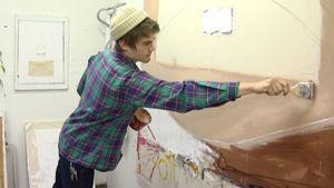 Kuvassa opiskelija Otso-Pekka Suhonen maalaa taulua.
