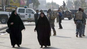 Kaksi mustaan burkhaan pukeutunutta naista. Taustalla