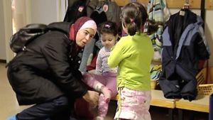 Ulkomaalaistaustainen nainen pukee lapsia päiväkodissa.