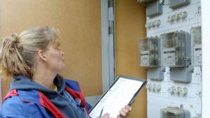 Nainen ottaa muistiin sähkömittarin lukuja