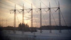 Kuvassa voimalinjaa talvisessa maisemassa.