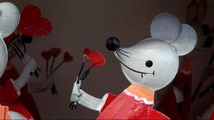 Metallista tehty herttainen hiiri, jolla on punainen mekko ja käpälässään sydämenmuotoisia kukkia.
