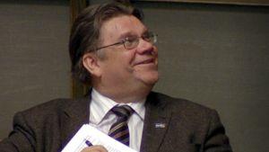 Perussuomalaisten puheenjohtaja Timo Soini istuu eduskuntasalissa ja hymyilee.