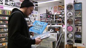 Mies selailee vinyylilevyjä levykaupassa