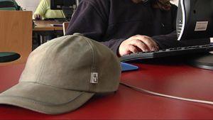 lippalakki pöydällä, lapsi tietokoneen ääressä