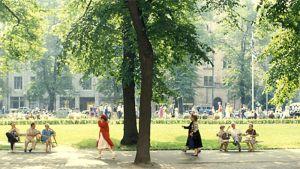Ihmisiä kavelee ja istuskelee aurinkoisessa Esplanadin puistossa Helsingissä.
