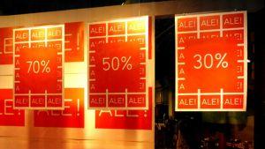 Alennusmyynnistä kertovia mainosjulisteita kaupan ikkunavitriinissä.
