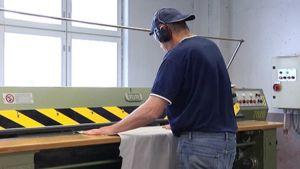 Mies käsittelee koneella nahkaa Ahlskog Leatherin tehtaalla Kruunupyyssä.