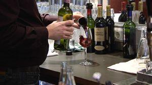 Baarimikko kaatamassa viiniä