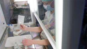 laboratoriotyöntekijä valuttaa pussista valutetaan näytettä mitta-astiaan, työntekijällä hengityssuojain ja valkoinen työasu.