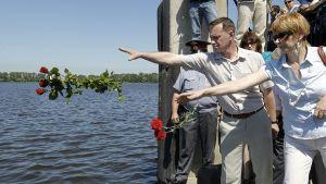 Ihmiset heittävät ruusuja veteen hukkuneiden muistotilaisuudessa