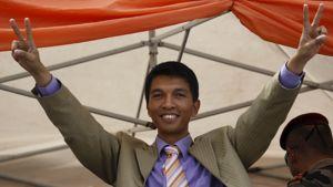 Andry Rajoelina hynyilee ja näyttää sormillaan voitonmerkkiä.