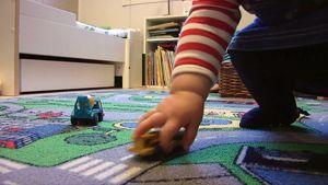 Lapsi leikkimässä pikkuautolla.
