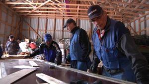 Miehet rakentavat herätysjuhlien rakenteita.