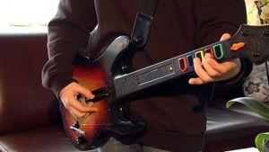 Poika soittaa Guitar Hero -tyyppisiä pelejä varten tarkoitetulla kitaralla.