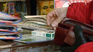 Nainen ostaa tupakkaa kioskilta
