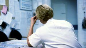 Väsynyt sairaanhoitaja taukohuoneessa yövuoron aikana.