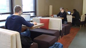 Ihmisiä käyttämässä langatonta internet-yhteyttä kahvilassa