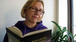 Kemiläinen kirjailija Eija Jansson käsissään tuorein teoksensa, kummitustarina Kielletyt huoneet.