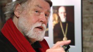 Valokuvaaja C. G. Hagström kokoamassa näyttelyään Sinebrychoffin taidemuseossa Helsingissä. Taustalla hänen ottamansa kuva arkkipiispa Paavalista.