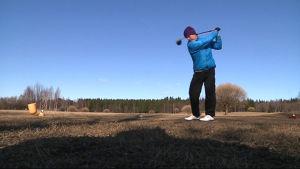 Golfaaja lyö palloa.