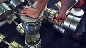 Miehen käsi nostaa raskasta, metallista käsipainoa.