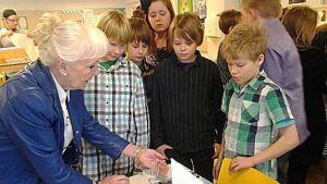 Kaarina Suonperä neuvoo koululaisille hyviä pöytätapoja.