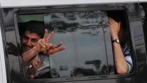 Syyriasta Turkkiin paenneet pakolaiset näyttävät voitonmerkkejä ohiajavasta kulkuneuvosta.