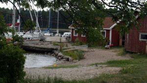 Helsingholm: punamultaista puuseinää ja valkoisia mastoja.