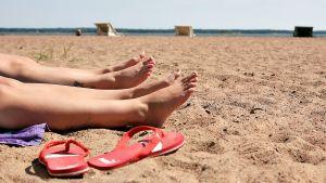 Naiset ottavat aurinkoa uimarannalla