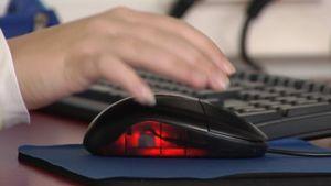 Käsi tavoittelee tietokonehiirtä.