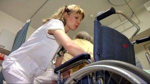 Sairaanhoitaja avustaa pyörätuolipotilasta