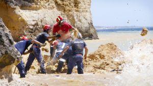 Palomiehet etsivät kiven alle hautautuneita ihmisiä uimarannalla.