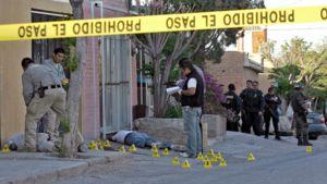 Keltaisen teipin sisäpuolella murhatutkimusta tekeviä poliiseja. Kaksi kuollutta ihmistä makaa maassa.