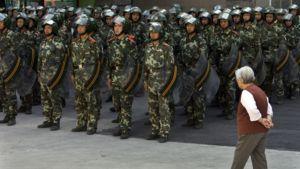 Vanha kiinalaisnainen käveli järjestäytyneen turvallisuusjoukon ohi heinäkuussa Urumqissa Xinjiangin maakunnassa Kiinassa.